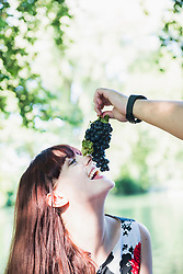 Man feeding grape to woman at lakeshore in the English Garden, Munich, Germany