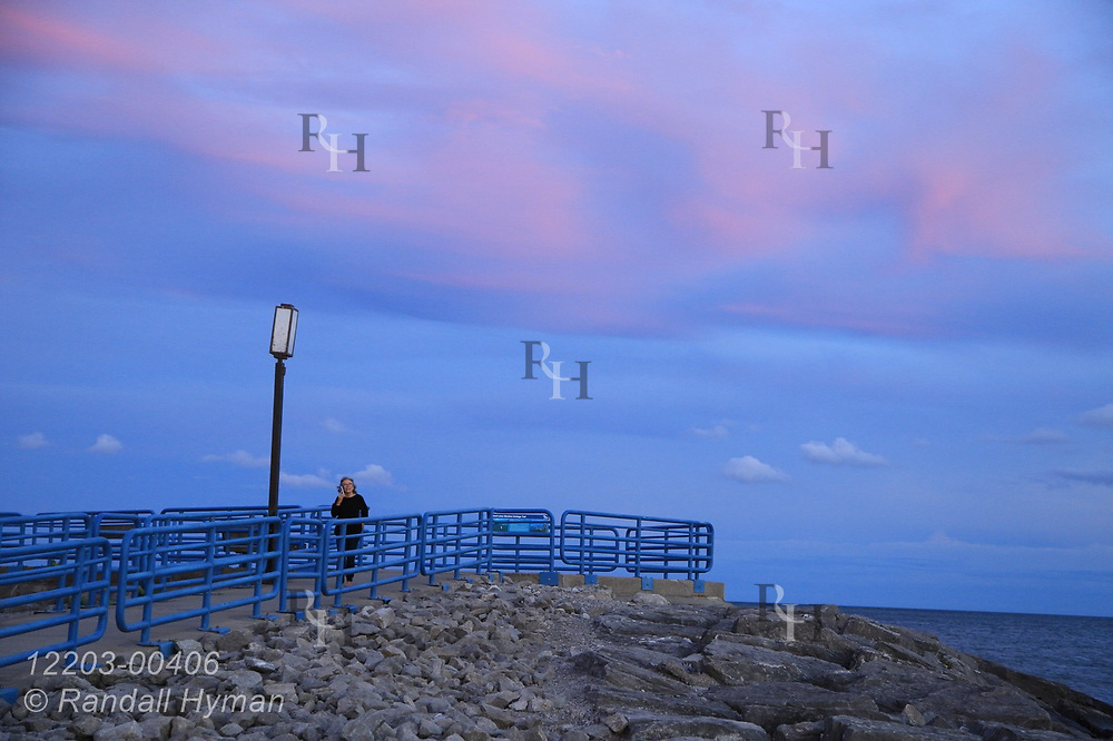 Woman talks on cell phone atop breakwater beneath rosy skies after September sunset in Alpena, Michigan.