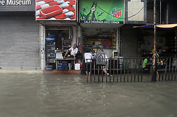 July 24, 2017 - Kolkata, West Bengal, India - Shop owner sits idle as there are very little customer due to overnight rain flooded the city street on July 24, 2017 in Kolkata. Overnight rain disrupted city life and causing flood like situation in several district of West Bengal resulting. Kolkata received 83 m.m. of rain in Monday morning. (Credit Image: © Saikat Paul/Pacific Press via ZUMA Wire)
