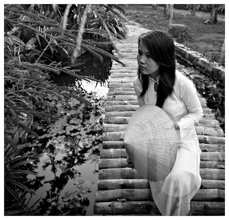 Beauty portrait of a vietnamese woman sitting on a bamboo bridge. She wears traditional outfit Ao Dai and conical hat. Kanh Hoa area, Vietnam, Asia