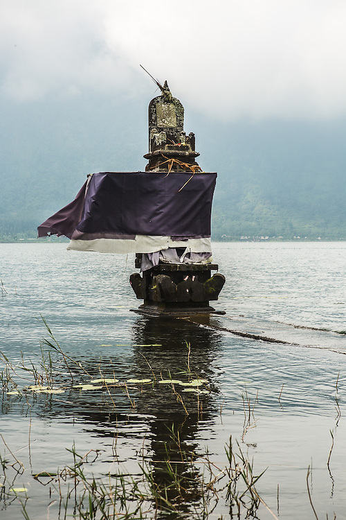 INDONESIA. Bedugul, Bali. June 4th, 2013. Inside the Pura Ulun Danu Bratan complex, this stone alter provides an offering on Lake Bratan.