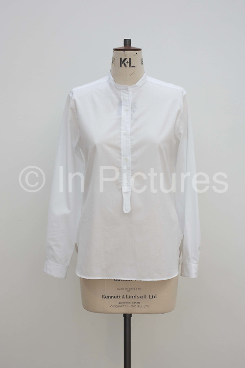 """A beautifully simple white cotton shirt by couturier Margaret Howell is displayed in the company's workshop factory in Edmonton, North London. England. Ironed without creases, the garment has been set on a dress making tailor's dummy made by Kennett and Lindsell of Romford Essex. The pure white shirt is seen against a similarly-toned white wall and lit by daylight. Howell is one of Britain's more understated of couture brands alongside more flamboyant personalities. Howell admits to being """"inspired by the methods by which something is made .. enjoying the tactile quality of natural fabrics such as tweeds, linen and cotton in a relaxed, natural and lived in look."""""""