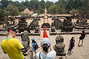 A woman in a red dress and bright pink hat poses for a photograph over the ancient site of Preah Ko temple, Roluos, Svay Chek District, Banteay Meanchey Province, Cambodia, South East Asia.  The temples were made of brick towers on a sandstone platform.