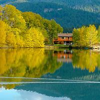 A house glows amongst fall colors in Mystic Heights Pond, near Bozeman, Montana.