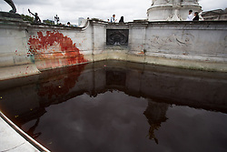 © Licensed to London News Pictures.  26/08/2021. London, UK. A number of Extinction Rebellion activists stained Victoria Memorial with artificial blood in front of Buckingham Palace in central London. Photo credit: Marcin Nowak/LNP