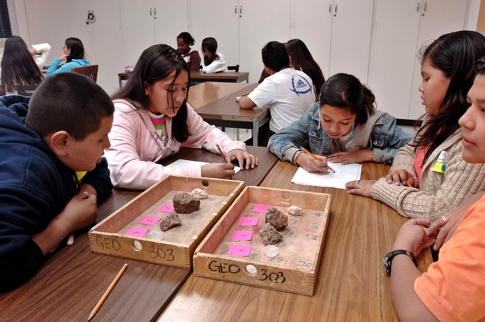 """Austin, Texas: Sixth-grade geology students observe the characteristics of a tray of rocks and minerals as part of a 'Science Olympiad"""" session at the University of Texas. The program helps college education students get practical experience teaching and exposes children to a college learning environment.  January 12, 2007 ©Bob Daemmrich /"""