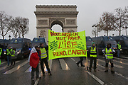 """December, 8th, 2018 - Paris, Ile-de-France, France: """"We also have to pay the ISF' Banner poster shown at Champs Elysees demonstration. The French 'Gilets Jaunes' demonstrate a fourth day. Their movement was born against French President Macron's high fuel increases. They have been joined en mass by students and trade unionists unhappy with Macron's policies. Nigel Dickinson"""