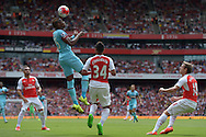 Diafra Sakho of West Ham United heads the ball over Francis Coquelin of Arsenal. Barclays Premier League, Arsenal v West Ham Utd at the Emirates Stadium in London on Sunday 9th August 2015.<br /> pic by John Patrick Fletcher, Andrew Orchard sports photography.