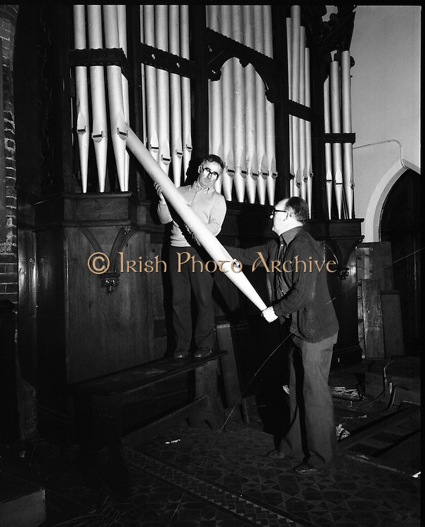 Pipe Organ Dismantling at Aungier Street.  (K86).1977..01.02.1977..02.01.1977..1st February 1977..A pipe organ built around 100 years ago for St Peter's Church (Church of Ireland),at Whitefriar / Aungier Street was being dismantled by Mr Gerry Smith and Mr Sam Wright of Dublin Organ Works. The organ was being dismantled for transfer to St Michael's Church,(Roman Catholic),in Blackrock,Co Cork..Mr Sam Wright and Mr Gerry Smith are pictured beginning the delicate operation of removing the organ pipes at the face of the organ.