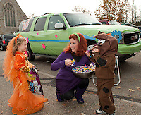 "Molly Hagan stops for some Scooby snacks from Daphne Blake (Lynne Turmel) and Scrappy-Doo (Bryce Turmel) alongside their Mystery Machine during the ""Trunk or Treat"" Halloween party Monday afternoon at Holy Trinity School in Laconia.  (Karen Bobotas/for the Laconia Daily Sun)"