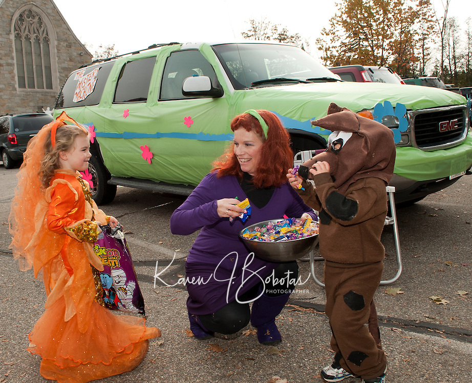 """Molly Hagan stops for some Scooby snacks from Daphne Blake (Lynne Turmel) and Scrappy-Doo (Bryce Turmel) alongside their Mystery Machine during the """"Trunk or Treat"""" Halloween party Monday afternoon at Holy Trinity School in Laconia.  (Karen Bobotas/for the Laconia Daily Sun)"""