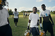 """BIRMINGHAM, AL – SEPTEMBER 10, 2015: Quintarius Monroe (center) speaks with Cornelius Mosley (right) as they break from football practice at Woodlawn High School. A type 1 diabetic, Monroe requires frequent blood sugar testing and supervision when self-administering insulin. When care from qualified personnel at his school in Center Point became unavailable, Monroe was forced to transfer several miles away from his locally zoned school to attend Woodlawn High School. The Americans with Disabilities Act requires schools to provide """"reasonable accommodation"""" for students with medical conditions, but given that most failing public schools no longer retain school nurses, many schools cannot provide adequate care for their students.<br /> CREDIT: Bob Miller for The New York Times"""