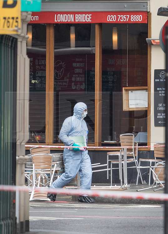 © Licensed to London News Pictures. 05/06/2017. London, UK. A police forensic officer passes a cafe in Borough Market as investigations continue following a terrorist attack on Saturday evening. Three men attacked members of the public  after a white van rammed pedestrians on London Bridge.   Ten people including the three suspected attackers were killed and 48 injured in the attack. Photo credit: Peter Macdiarmid/LNP