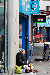A woman in a headscarf begs on Oxford Street outside a bureau de change. Homeless Britons are coming under increasing pressure as a surge of Roma beggars from Romania arrive on the streets of London to take advantage of the generosity of Christmas shoppers. London, December 04 2018.
