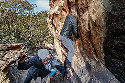 Sarah Hepola and guide Jacob Garza crossing narrow ledge at Hueco Tanks State Park & Historic Site, El Paso, Texas. USA.