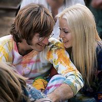 """John Sebastian with girlfriend.- .A man of many faces, clean shaven in The Lovin Spoonful, but now more relaxed as he was reunited with old colleague John Sebastian. Brian Hinton in his book """"Message to Love"""" remembers him as being ubiquitous and a symbol of permanence - almost as if his presence was dependent on the success of the festival, he seemed to be everywhere!"""