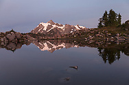 Earth's shadow behind Mount Shuksan reflected in a tarn at Huntoon Point in the Mount Baker-Snoqualmie Forest, Washington State, USA.