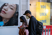 A young couple wearing face coverings walk past messaging about not locking down on love, outside the the Oxford Street branch of clothing retailer, Primark during the third lockdown of the Coronavirus pandemic, on 29th March 2021, in London, England.