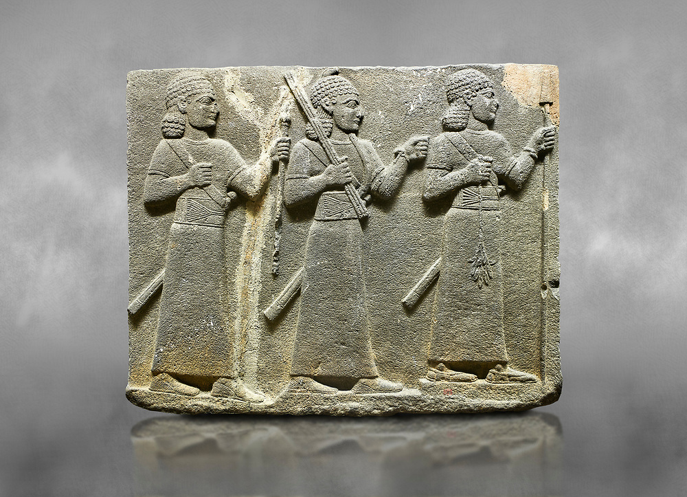 Hittite relief sculpted orthostat stone panel of Royal Buttress Basalt, Karkamıs, (Kargamıs), Carchemish (Karkemish), 900-700 B.C. Warriors. Anatolian Civilisations Museum, Ankara, Turkey.<br /> <br /> Three figures each with a long dress, a thick belt and curly hair. The figure in front holds a spear with a broken tip in his left hand and a leafy branch in his right hand. The figure in the middle made his left hand a fist, and he carries a tool with his right hand at the level of his head. They are followed with a figure holding a sceptre in his left hand. All three have each a long sword at their waist. <br /> <br /> Against a grey art background. .<br />  <br /> If you prefer to buy from our ALAMY STOCK LIBRARY page at https://www.alamy.com/portfolio/paul-williams-funkystock/hittite-art-antiquities.html  - Type  Karkamıs in LOWER SEARCH WITHIN GALLERY box. Refine search by adding background colour, place, museum etc.<br /> <br /> Visit our HITTITE PHOTO COLLECTIONS for more photos to download or buy as wall art prints https://funkystock.photoshelter.com/gallery-collection/The-Hittites-Art-Artefacts-Antiquities-Historic-Sites-Pictures-Images-of/C0000NUBSMhSc3Oo