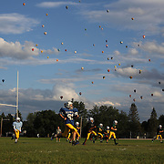 The Pennfield Bombers 7th grade American Football Team train in the late evening sunshine as Hot Air balloons take to the skies around rural Michigan near Battle Creek during the World Hot Air Ballooning Championships. Battle Creek, Michigan, USA. 20th August 2012. Photo Tim Clayton