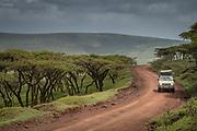 View of a 4x4 safari car driving along a dirt road, Ngorongoro Conservation area, Tanzania