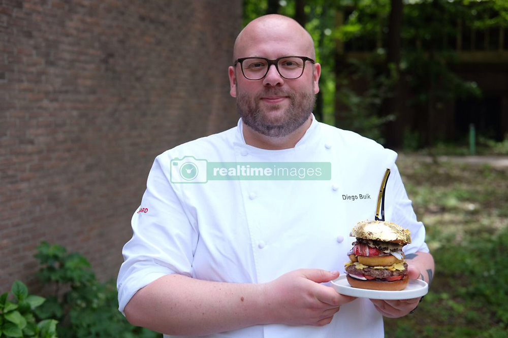 June 12, 2017 - inconnu - A chef has created the world's most expensive meaty burger that costs a whopping €2,050 Euros / $2,290 USD / £ 1,800 GBPThe burger confirmed as the world's priciest by Guinness World Records ,includes lobster, caviar, foie gras, and truffle.The beef patty in the world's priciest burger is a blend containing the most expensive steak in the world - a Japanese dry-aged Wagyu, while the other is a luxurious Black Angus beef steak.The lobster is infused with Hermit Dutch Coastal gin, while other prime toppings include artisan Remeker cheese, Japanese fruit tomatoes and pricey Iberian ham.The burger sauce is made using lobster and a host of other top-quality ingredients that reads like a gourmand's dream shopping list: Jamaican Blue Mountain Coffee, Madagascan vanilla, saffron, and Japanese soy.And to top it all off, the brioche burger bun , worth €120 on its own) is covered in 24 karat gold leaf.Dutchman Buik, chef at the South of Houston restaurant in The Hague, said he created the pricey sandwich to earn a spot in the Guinness Book of World Records.He had already made and sold 100 different types of limited edition burgers to celebrate selling 15,000 burgers at his previous workplace in just six months.But this time, he wanted to try something truly headline-grabbing to celebrate International Hamburger Day on May 28. The total cost of ingredients for his pricey burger came to €1,000 before he had even started cooking with them.He said his love of burgers stems from his time working for Soho House in London for two years.His gold leaf-topped burger doesn't feature on his restaurant's menu, but he said he would be willing to make it for someone if they asked for it.Buik, whose love of burgers stems from his time working for Soho House in London for two years, said his pricey burger - though delicious - is not the best he's ever eaten. He said that was one her ate at a Byron restaurant in the UK which cost him just #€1