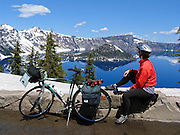 Bicycle in view of Wizard Island, which rises in the deep blue lake at Crater Lake National Park, in Oregon, USA. To allow snow plowing in early June, Rim Drive is closed to cars but open to bicycles, making an excellent time for a bike ride free of automobiles. Published in August 2015 issues of Alaska Airlines & Horizon Edition inflight magazines. Published on BikeGrandCanyon.com and on a poster for their affiliated BikeYourPark.org.