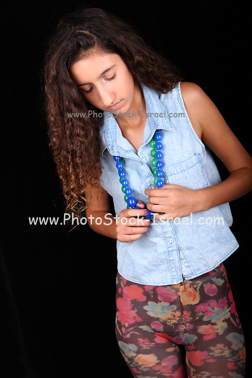 Studio shot of Young teen in blue top and floral pants on black background
