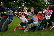 Local children from varying family backgrounds and ethnicities get stuck in with a heave-ho on a large rope for the best of three tug war games during a community park festival. As part of an annual event in Ruskin Park in the London borough of Lambeth, neighbours and friends meet for an afternoon of self-initiated events including this contest of strength and teamwork. Both big kids and younger people join in and either help pull or simply hang on as the rope on their side either wins or loses.