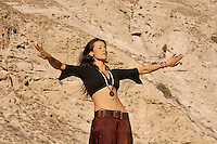 Woman dancing with her eyes closed within and her arms like wings in a desert landscape.