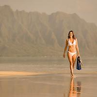 female walking exposed sand bar in Kaneohe Bay, Koolau Mountains at Kualoa as backdrop.