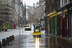 Edinburgh, Scotland, UK. 31 December 2020. Views of streets in Edinburgh during level 4 Covid-19 lockdown. Few people on the streets as all shops and cafes are closed.  Pic; A tractor gritting the pavements is the only vehicle on the Royal Mile. Iain Masterton/Alamy Live News
