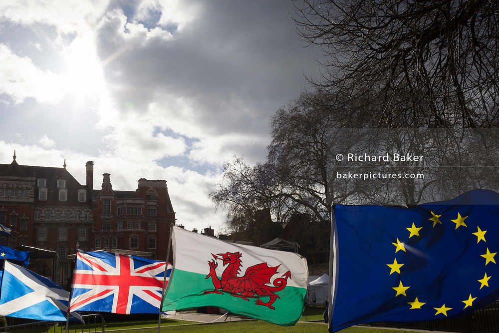 As Prime Minister Theresa May negotiates further Britain's exit from the European Union in Brussels, the EU flag and that of the Welsh, the Union Jack and the Scottish Saltair fly in a stiff breeze on College Green, as part of an anti-Brexit protest opposite the Houses of Parliament, on 7th February 2019, in Westminster, London England.