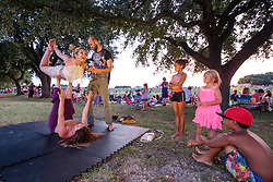 Kids watching people practicing yoga and acrobatic moves at July 4th celebration on the Trinity Trails near the Panther Island Pavilion, Trinity River, Fort Worth, Texas, USA.
