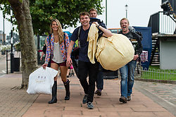 © Licensed to London News Pictures. 05/09/2014. Isle of Wight, UK. Festival goers arrive at the port of Ryde on the Isle of Wight on their way to Bestival 2014 on day 2 Friday of the music festival carrying their tents and food & drink suppliers for the weekend. Photo credit : Richard Isaac/LNP