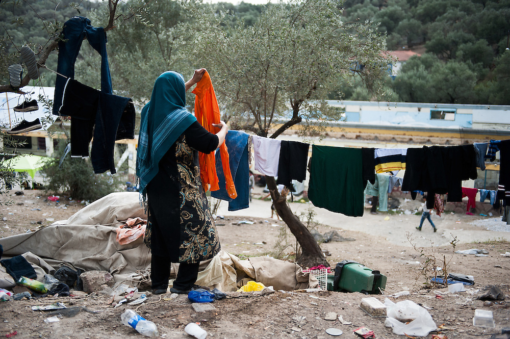 An Afghan woman hangs clothes on a makeshift washing line at Moria camp, Lesvos, Greece.