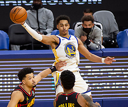 Mar 26, 2021; San Francisco, California, USA; Golden State Warriors guard Jordan Poole (3) leaves his feet to pass over Atlanta Hawks forward John Collins (20) during the fourth quarter of an NBA basketball game at Chase Center. Mandatory Credit: D. Ross Cameron-USA TODAY Sports