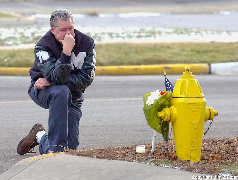 """Kevin Burnett, 51, of South Bend, wrestles with the """"stupidity"""" of shooting two Mishawaka police officers as he stops at a small memorial at the intersection of Broadway Street and Sarah Street, just a half a block from the home where the officers were shot.   Burnett, a 1970 graduate of Marion High School, said that he new Cpl. Thomas Roberts, often playing basketball with him in pickup games when they were growing up in Mishawaka.  Cpl. Thomas and Patrolman Bryan Verkler were killed in the line of duty in December of 2003."""