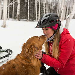 A woman and her golden retriever take a break from fat tire biking on a snowy winter day in New Hampshire's White Mountains.