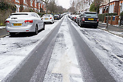 Looking uphill, an urban landscape scene of a light dusting of snow that has covered the road surface of a residential street in Herne Hill, SE24, Lambeth, south London where cars are parked on both sides outside their owners houses, on 8th February 2021, in London, England.