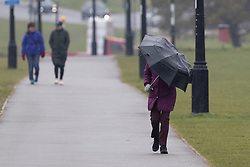 © Licensed to London News Pictures. 10/03/2021. London, UK. A woman shelters from wet and windy weather as she walks on Blackheath Common in South East London . A yellow weather warning for wind is in place in parts of the UK. Photo credit: George Cracknell Wright/LNP