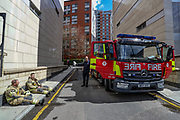 London, Britain, May 7, 2021 — Firefighters are seen taking a break after they tackled a blaze in a 19-storey block of flats in east London on Friday, May 7, 2021. (Photo/ Vudi Xhymshiti)