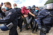 German police officers detain a protester during a demonstration in front of the Reichstag building, seat of the German parliament the Bundestag in Berlin, Germany, 16 May 2020. A series of demonstrations throughout Germany, calling for ending of the social and economical restrictions imposed due to the coronavirus pandemic. The events are organized by groups of various motives, right wing activists, conspiracy theory believers and more.