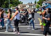 An Elk Grove police officer blocks traffic as protesters march for George Floyd in Elk Grove on Wednesday, June 10, 2020.