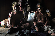 Penan elderly couple, the man still wears the old style chawat loincloths. They where nomadic a few decades ago. The Penan native people are learning to live a sedentary lifestyle which includes living in wooden houses, farming and fishing. They were traditionally nomadic hunter-gatherers. These days they have become forcibly settled as their hunting grounds have been largely destroyed by logging concessions and palm-oil plantations. Long Napir, Limbang, Sarawak Malaysia 2015<br /> <br /> There are only a few, difficult to find, scarce communities of semi-nomadic Penan nowadays, who live like of those of old, hidden away deep in the tropical forest, hunter-gathering, wearing loin cloth 'chawats', hunting wild boar with blowpipes and poison arrows, and extracting sago-root flour, their staple carbohydrate, by hand.<br /> <br /> Borneo native peoples and their rainforest habitat revisited two decades later: 1989/1991 and 2012/2014/2015. <br /> <br /> Sarawak's primary rainforests have been systematically logged over decades, threatening the sustainable lifestyle of its indigenous peoples who relied on nomadic hunter-gathering and rotational slash & burn cultivation of small areas of forest to survive. Now only a few areas of pristine rainforest remain; for the Dayaks and Penan this spells disaster, a rapidly disappearing way of life, forced re-settlement, many becoming wage-slaves. Large and medium size tree trunks have been sawn down and dragged out by bulldozers, leaving destruction in their midst, and for the most part a primary rainforest ecosystem beyond repair. Nowadays palm oil plantations and hydro-electric dam projects cover hundreds of thousands of hectares of what was the world's oldest rainforest ecosystem which had some of the highest rates of flora and fauna endemism, species found there and nowhere else on Earth, and this deforestation has done irreparable ecological damage to that region