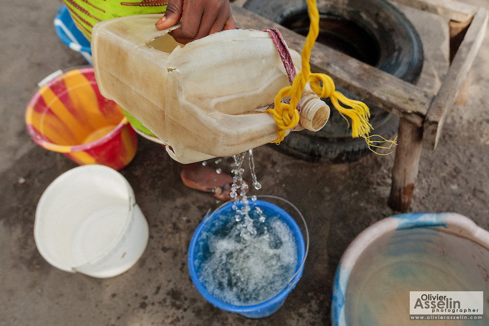 A teenage girl draws water from a well next to a UNICEF-sponsored public latrine in the Point Four neighborhood of Monrovia, Montserrado county, Liberia on Thursday April 5, 2012. Residents can use the facility for a fee of 5 liberian dollars (approx. 0.07  USD). The money collected serves is used for maintenance.