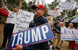 August 15, 2017 - Vista, California, U.S. - SEAN COLGAN of Oceanside, center, on the motorcycle, along with pro and anti-Trump, and Congressman Darrell Issa supporters, let their different opinions be heard outside Issa's Vista office during the weekly rally. (Credit Image: © Howard Lipin/San Diego Union-Tribune via ZUMA Wire)