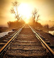 Railroad tracks into the sunrise near the Provo River on a foggy late winter morning.