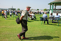 © Licensed to London News Pictures.16/07/15<br /> Harrogate, UK. <br /> <br /> A man walks across the President's Green as he visits on the final day of the Great Yorkshire Show.  <br /> <br /> England's premier agricultural show has seen three days of showcasing the best in British farming and celebrating the countryside.<br /> <br /> The event which attracts over 130,000 visitors each year displays the cream of the country's livestock and offers numerous displays and events giving the chance for visitors to see many different countryside activities.<br /> <br /> Photo credit : Ian Forsyth/LNP
