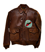 """This type A-2 flight jacket belonged to William E. Hofer, a radio operator attached to the 568th squadron of the 390th Bomb Group. The 568th squadron insignia patch, a panther riding a bomb, is attached to the front left of the jacket. The 8th Air Force insignia patch is attached to the left sleeve of the jacket. The name of Hofer's aircraft, """"Ole Smoke"""", is painted in yellow on the back of the jacket. Hofer flew 23 missions over Europe as a member of the 568th squadron. On his 23rd mission, a raid to Augsburg, Germany on March 16, 1944, Hofer and his crew were shot down over Germany and taken as prisoners of war by the Germans."""